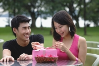 Woman unwrapping a gift, man crouching next to her, smiling - Asia Images Group