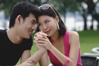 Couple sitting side by side, face to face, holding hands - Asia Images Group