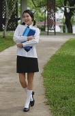 Young woman in school uniform, walking on path - Asia Images Group