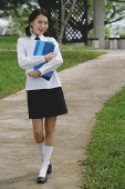 Young woman in school uniform, walking on path, smiling at camera - Asia Images Group