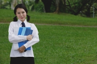 Young woman in school uniform, standing in park - Asia Images Group