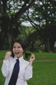 Young woman in school uniform, standing in park, touching her hair - Asia Images Group