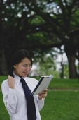 Young woman in school uniform, reading a book - Asia Images Group