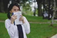 Young woman in school uniform, book covering face - Asia Images Group