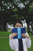 Young woman in school uniform, book covering face, looking away - Asia Images Group