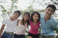 Young adults in park, smiling at camera - Asia Images Group