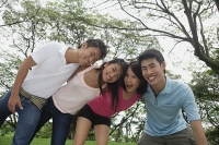 Young adults in park, side by side, embracing - Asia Images Group