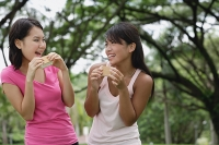 Two women eating ice cream, smiling - Asia Images Group