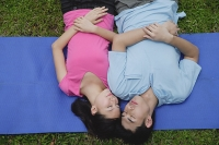 Couple in park, lying on mat, eyes closed - Asia Images Group