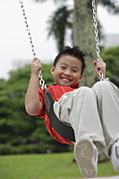 Boy swinging, smiling at camera - Asia Images Group