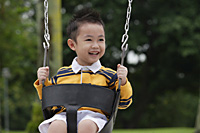 Young boy on playground swing, smiling, looking away - Asia Images Group