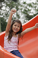 Girl coming down playground slide, arms outstretched - Asia Images Group