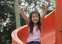 Girl coming down playground slide, arms outstretched, smiling at camera - Asia Images Group