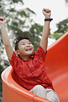 Boy coming down playground slide, arms outstretched, smiling, looking up - Asia Images Group