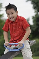 Boy sitting on See-Saw, smiling at camera - Asia Images Group