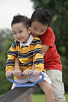 Two brothers sitting on See-Saw - Asia Images Group