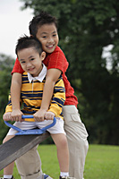 Two brothers sitting on See-Saw, smiling at camera - Asia Images Group
