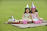 Two girls wearing party hats sitting on picnic blanket, surrounded by gifts - Asia Images Group