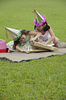 Two girls wearing party hats sitting on picnic blanket, opening a gift - Asia Images Group
