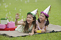 Two girls wearing party hats lying on picnic blanket, looking at bubbles - Asia Images Group