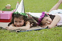 Two girls wearing party hats lying on picnic blanket, resting - Asia Images Group