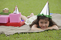 Girl lying on picnic blanket, wearing party hat, smiling at camera - Asia Images Group