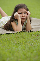 Girl lying on picnic blanket, hands on face, sad expression - Asia Images Group