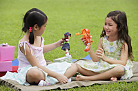 Two girls sitting on picnic blanket, playing with dolls - Asia Images Group