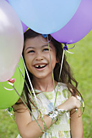 Young girl with several balloons, smiling - Asia Images Group