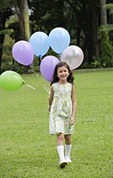 Girl walking on grass, holding a bunch of balloons - Asia Images Group