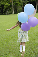 Girl walking on grass, holding balloons, rear view - Asia Images Group