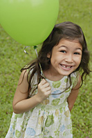 Girl holding green balloon, smiling at camera - Asia Images Group