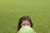 Girl hiding behind green balloon - Asia Images Group