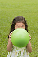 Girl standing on grass, holding green balloon over her face - Asia Images Group