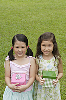 Two girls with gift boxes, standing side by side, smiling at camera - Asia Images Group