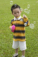 Boy blowing bubbles from bubble wand - Asia Images Group