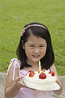 Girl holding birthday cake with one candle - Asia Images Group