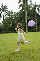 Girl running in park, purple balloon flying behind her - Asia Images Group