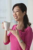 Mature woman holding cup, smiling, looking away - Asia Images Group
