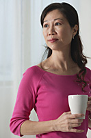 Mature woman holding cup, looking away - Asia Images Group