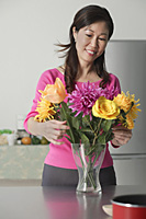 Mature woman arranging flowers in vase - Asia Images Group