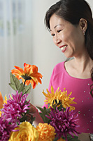 Mature woman looking at flowers, smiling - Asia Images Group