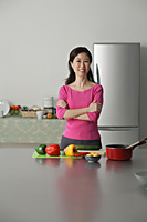 Mature woman in kitchen, arms crossed, looking at camera - Asia Images Group