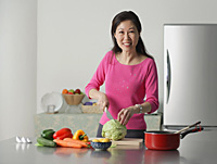 Mature woman in kitchen, preparing food - Asia Images Group