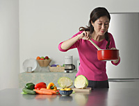 Mature woman cooking in kitchen, looking at contents of pot - Asia Images Group