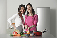 Mother and adult daughter in kitchen preparing a meal, looking at camera - Asia Images Group