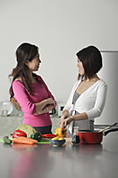 Mother and adult daughter in kitchen preparing a meal, looking at each other - Asia Images Group