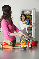 Mother and adult daughter in kitchen, daughter at refrigerator, holding bell pepper - Asia Images Group