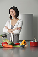 Young woman in kitchen, arms crossed, vegetables on the table in front of her - Asia Images Group