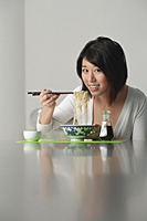 Young woman sitting and eating a bowl of noodles - Asia Images Group